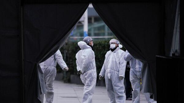 Медики в защитных костюмах на железнодорожной станции Шанхая