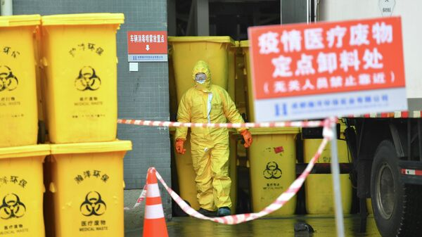 Работник центра утилизации медицинских отходов в защитном костюме в городе Чэнду