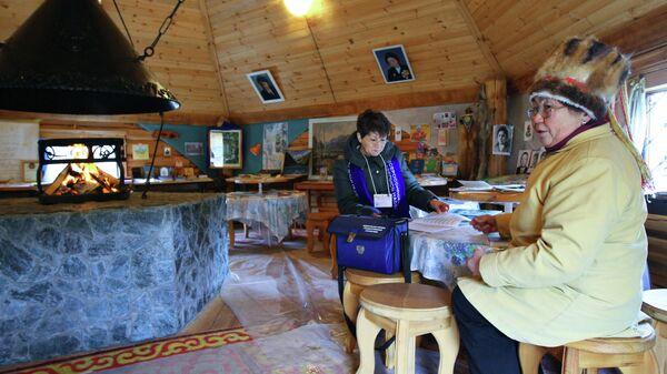 Сотрудник службы переписи населения проводит перепись хозяйки и смотрителя алтайского домашнего центра-музея в селе Чемал в республике Алтай