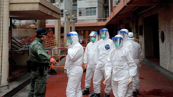 Полицейские в защитных костюмах во время эвакуации жителей из жилого дома в Гонконге