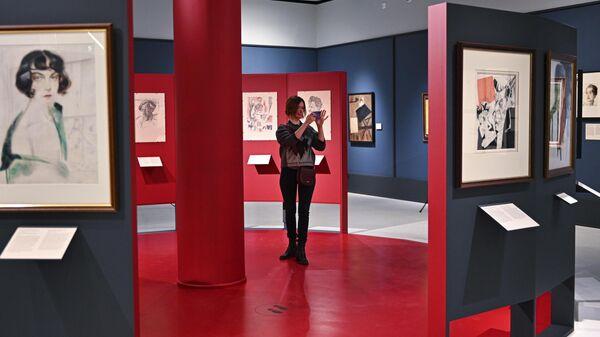 Посетительница фотографирует картины на выставке художника Юрия Анненкова Революция за дверью в музее русского импрессионизма в Москве