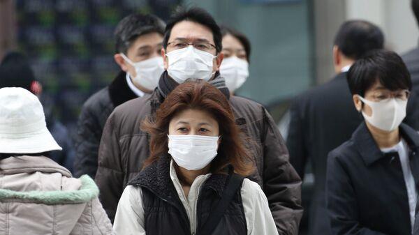 Прохожие в защитных масках на улице Токио, Япония