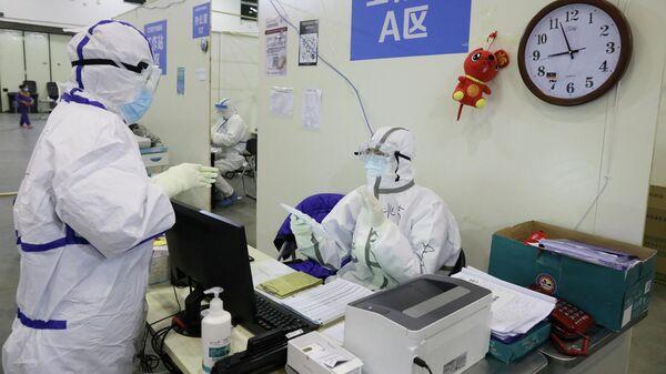 Медицинские работники в защитных костюмах во временной больнице в городе Ухань