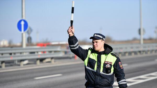 Сотрудник дорожно-патрульной службы подает сигнал водителю об остановке у стационарного поста ДПС