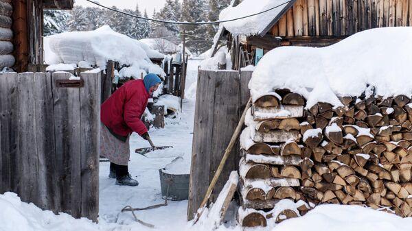 Женщина чистит снег во дворе дома в селе Омской области