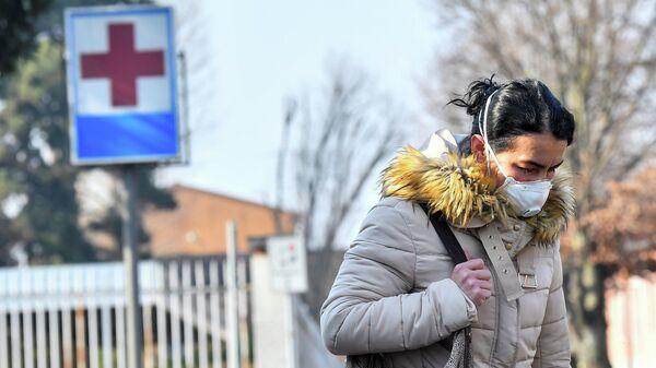 Женщина в защитной маске покидает больницу Кодоньо в северной Италии