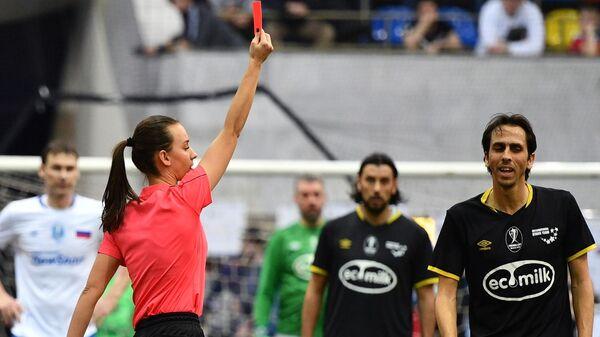 Главный судья Александра Пономарева показывает красную карточку игроку сборной Звезд Йосси Бенаюну