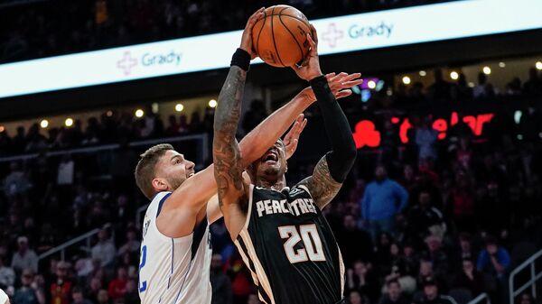 Форвард Атланты Хоукс Джон Коллинз в матче НБА против Макси Клебера из Даллас Маверикс