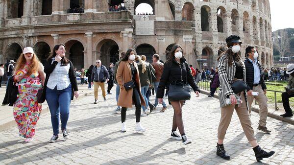 Люди в защитных масках у Колизея в Риме, Италия