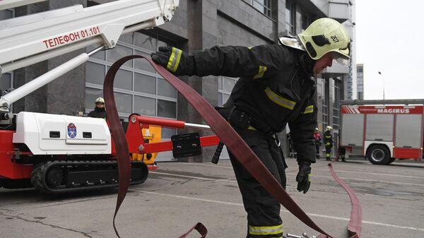 Сотрудник пожарно-спасательного центра Москвы монтирует пожарный рукав