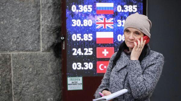 Женщина около пункта обмена валют в Киеве