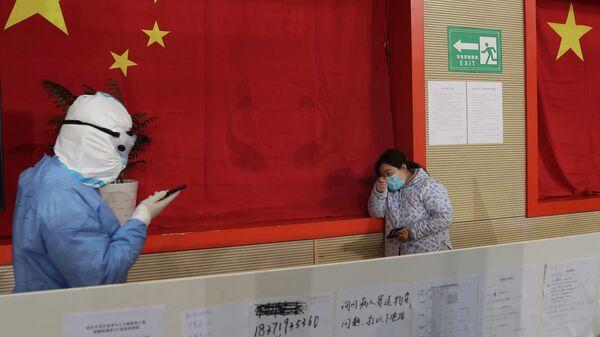 Медицинский работник в защитном костюме во временной больнице для лечения пациентов с новым коронавирусом в городе Ухань, провинция Хубэй