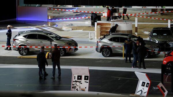 Автомобили и рабочие в выставочном центре Palexpo в Женеве, где должен был пройти Международный автосалон