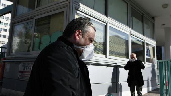 Люди, одетые в защитные маски, около больницы AHEPA, где проходит лечение первый пациент с подтвержденным   коронавирусом, в Салониках, Греция