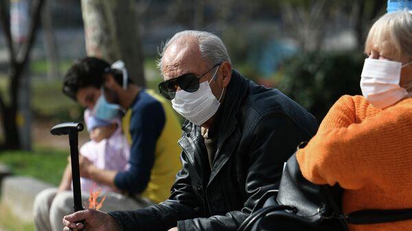 Люди, одетые в защитные маски, около больницы AHEPA, где проходит лечение первый пациент с подтвержденным   коронавирусом в Салониках, Греция