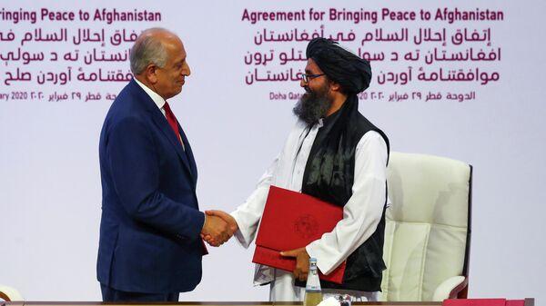 Мулла Абдул Гани Барадар, глава делегации талибов, и Залмай Халилзад, посланник США по вопросам мира в Афганистане, после подписания соглашения в Дохе, Катар. 29 февраля 2020