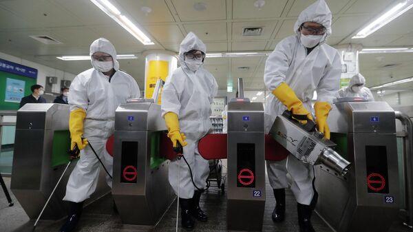 Медицинские работники проводят дезинфекцию на станции метро в Сеуле, Южная Корея