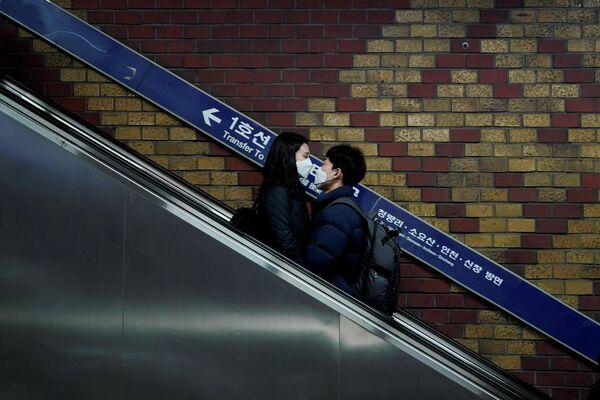 Пара в медицинских масках на эскалаторе в Сеуле