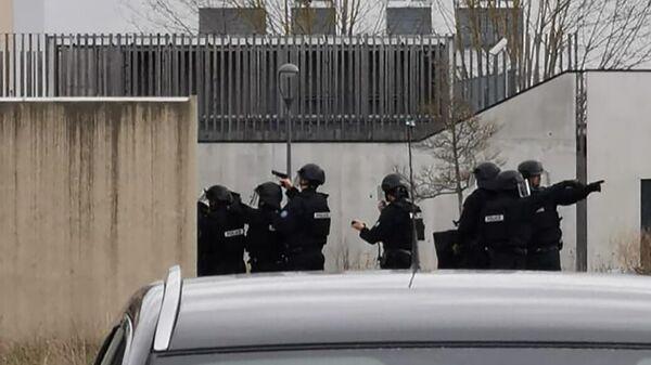 Сотрудники полиции во французском городе Труа, где вооруженный мужчина взял в заложники беременную женщину и пятерых детей. Фотография очевидца
