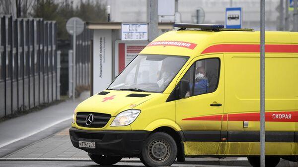 Машина скорой помощи заезжает на территорию больничного комплекса