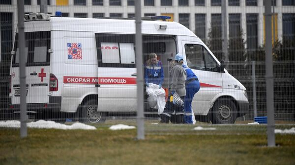 Сотрудники скорой помощи надевают защитные костюмы на территории больничного комплекса в Коммунарке