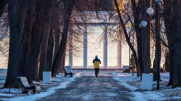 Молодой человек бежит по бульвару к набережной Онежского озера в Петрозаводске