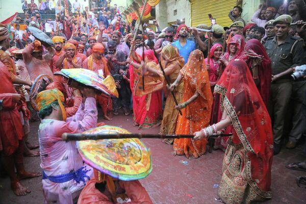 Женщины избивали мужчин палками во время празднования Латмар Холи в деревне Барсана, Уттар-Прадеш в Индии