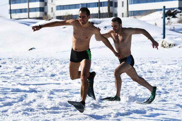 Члены клубов зимнего плавания и закаливания проводят забег в ластах во время празднования Широкой Масленицы на озере Юго-Западного жилого массива в Новосибирске