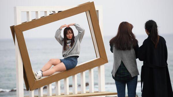Девушки фотографируются на пляже Gyeongpo Beach в городе Каннын, Республика Корея