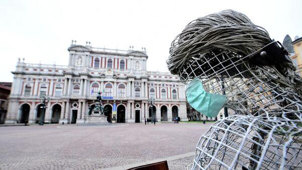 Защитная маска на скульптуре в Турине, Италия