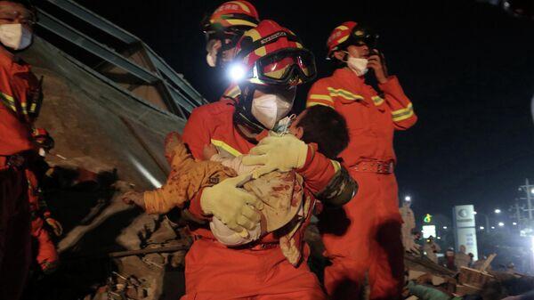 Спасатель выносит ребенка из-под обломков  отеля  Xinjia Express, рухнувшего в китайской провинции Фуцзянь
