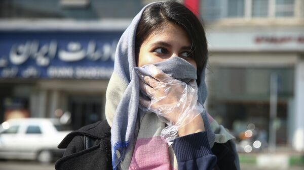 Девушка прикрывает лицо платком на улице Тегерана, Иран