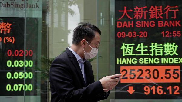 Мужчина в защитной маске на фоне табло с котировками ценных бумаг в Гонконге