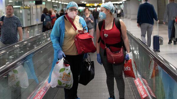 Туристы в защитных масках в аэропорту Суварнабхуми в Бангкоке