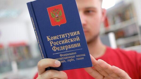 Молодой человек держит Конституцию РФ