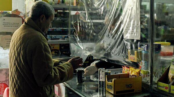 Продавец в защитных перчатках продает банку пива в одном из магазинов Мадрида