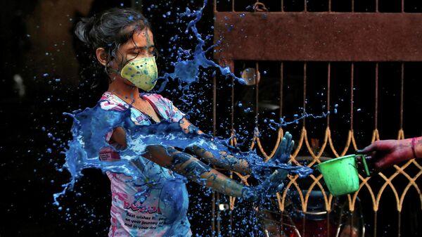 Девушка в защитной маске во время празднования Холи в Ченнаи, Индия