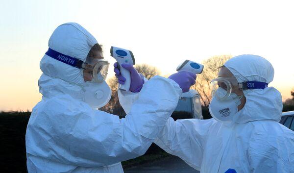 Медицинские работники проверяют температуру друг у друга на границе Италии и Словении