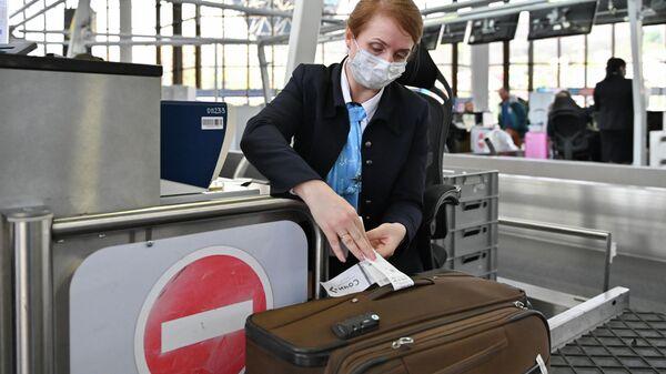 Сотрудница авиакомпании производит регистрацию пассажиров и багажа на рейс в Международном аэропорту Сочи