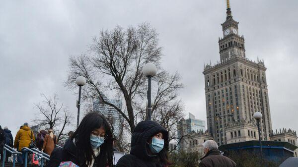 Прохожие в медицинских масках на улице в Варшаве