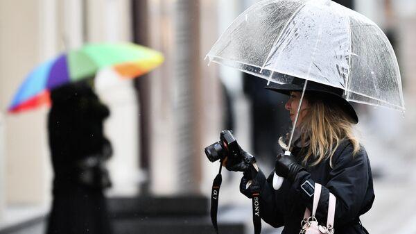 Девушка с фотокамерой во время пасмурной погоды в Москве