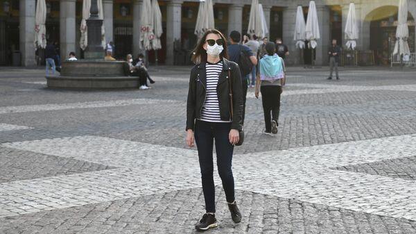 Девушка в защитной маске на площади Пласа-Майор в центре Мадрида
