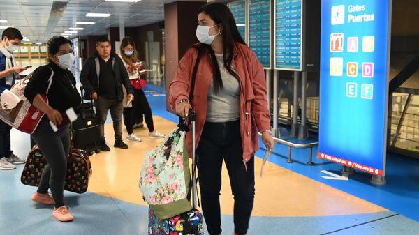 Пассажиры в защитных масках в международном аэропорту Барахас в Мадриде