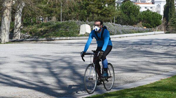 Мужчина на велосипеде в защитной маске парке Каса-де-Кампо в Мадриде