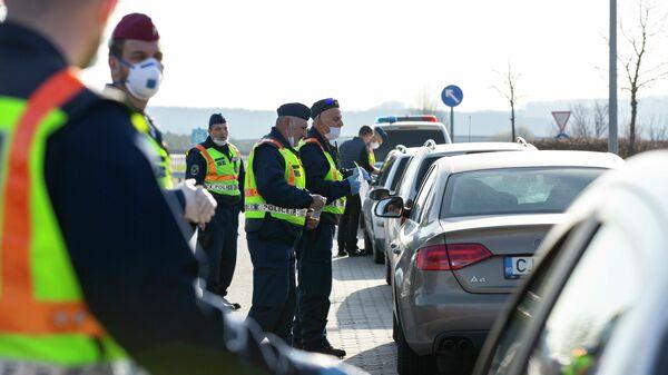 Венгерские полицейские проверяют документы у водителей, прибывших из Словении, в связи с усиленным контролем из-за эпидемии коронавируса