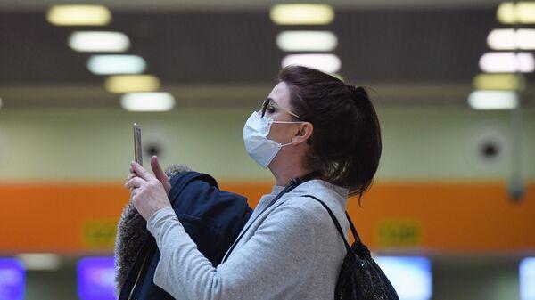 Женщина в медицинской маске в аэропорту Шереметьево