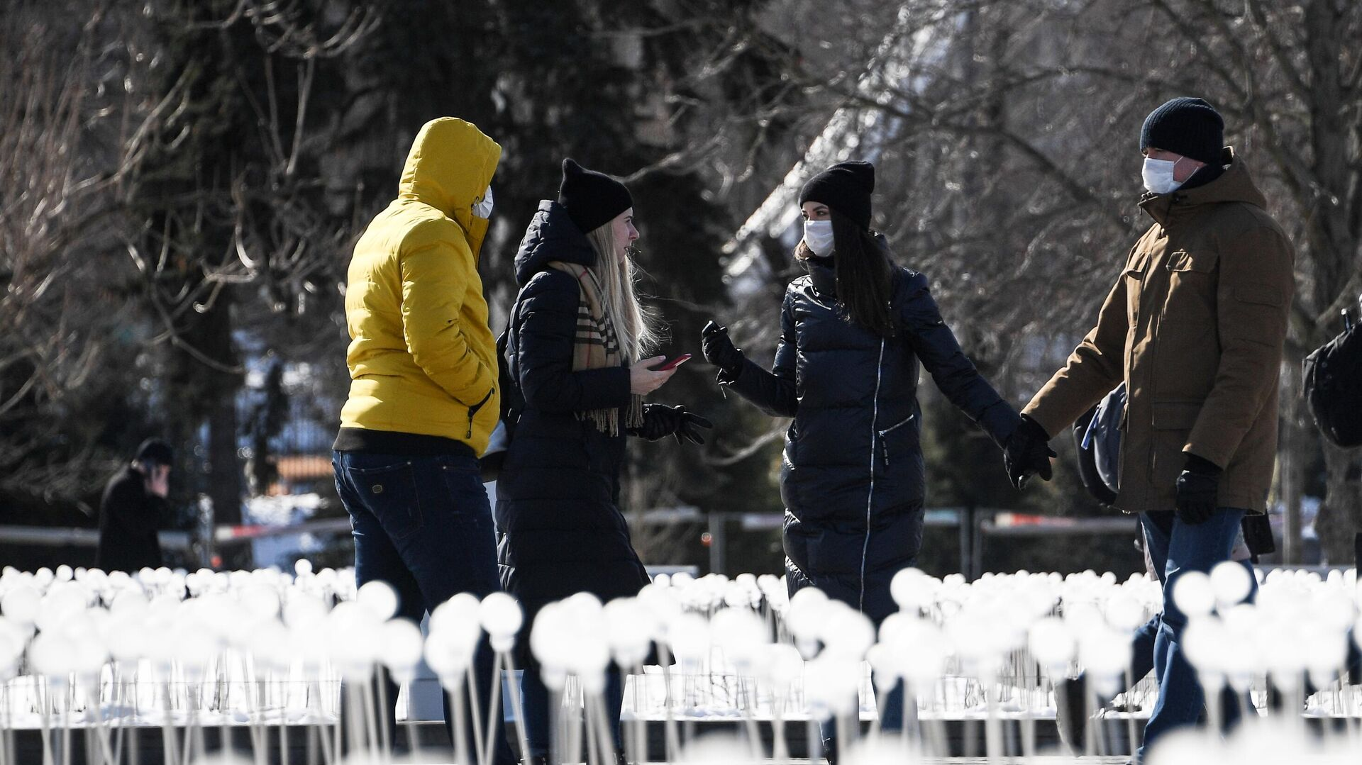 Молодые люди в медицинских масках гуляют на ВДНХ в Москве - РИА Новости, 1920, 20.03.2021
