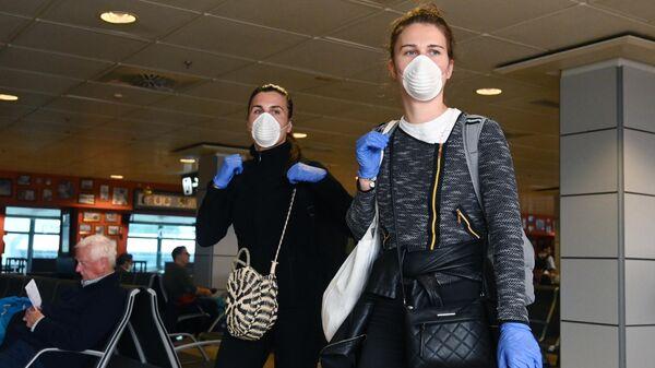 Пассажиры в медицинских масках в аэропорту Мадрида