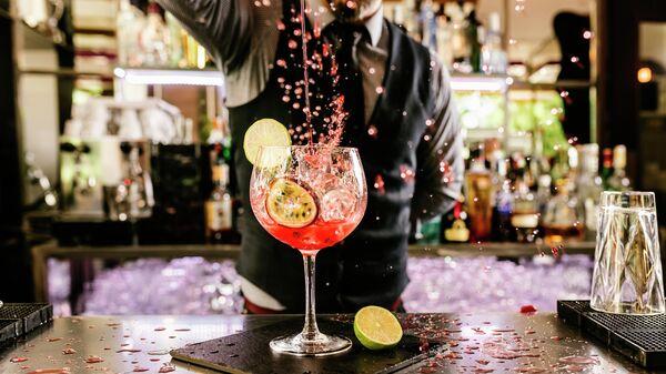 Бармен ночного клуба делает коктейль