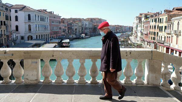 Мужчина на мосту Риальто в Венеции